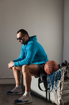 Side view of man in hoodie and sunglasses with basketball next to him