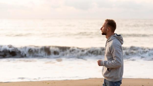 ビーチでジョギングする側面図の男
