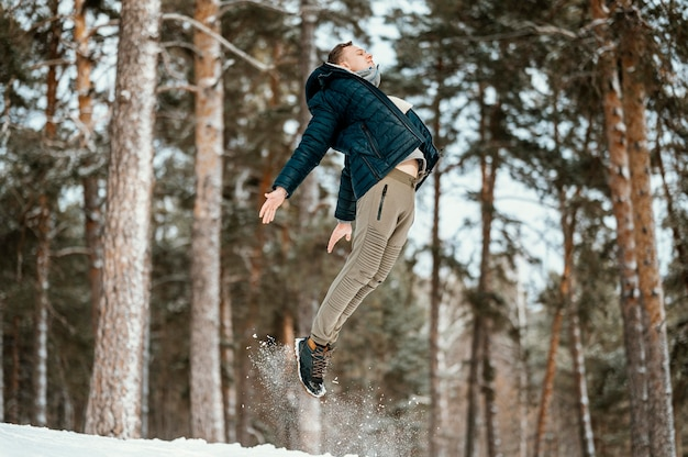 Side view of man jumping outdoors in nature during winter