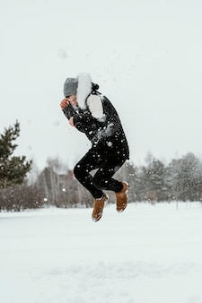 Side view of man jumping outdoors in winter