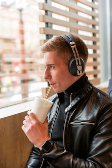 Side view man listening to music on headphones inside