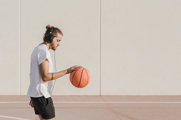 Side view of a man listening to music while practicing basketball