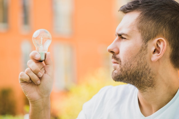 Side view of man looking at light bulb