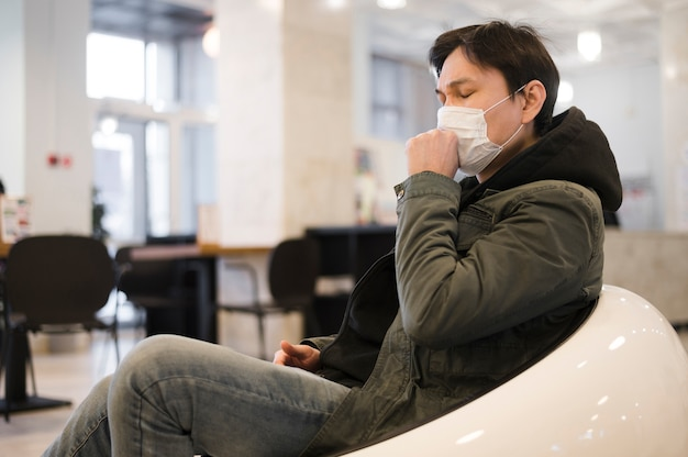 Side view of man lounging and coughing in medical mask