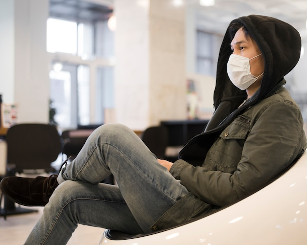 Side view of man lounging while wearing a medical mask