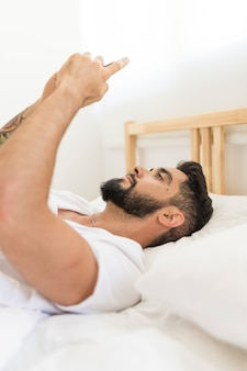 Side view of a man lying on bed holding mobile phone