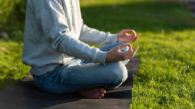 Uomo di vista laterale che medita sull'erba