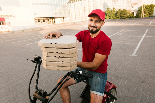 Side view man on motorcycle holding pizza boxes