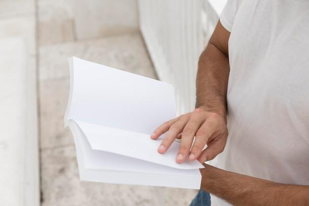 Vista laterale dell'uomo all'aperto che tiene libro