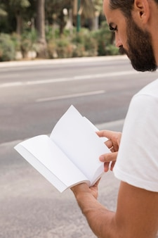 Side view of man outdoors reading from book