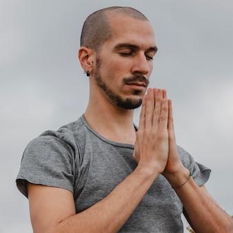 Vista laterale dell'uomo fuori facendo yoga