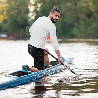 Side view man paddling in canoe