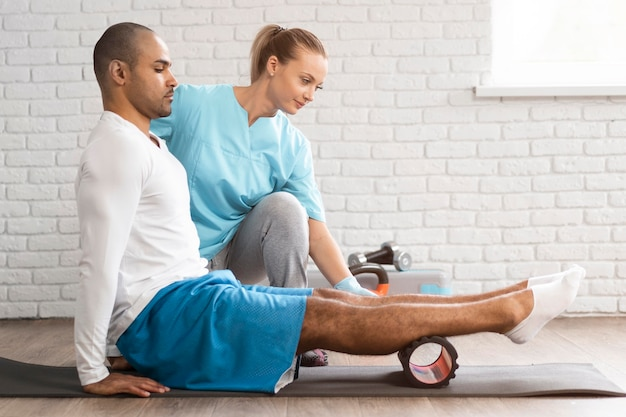 Side view of man and physiotherapist doing exercises