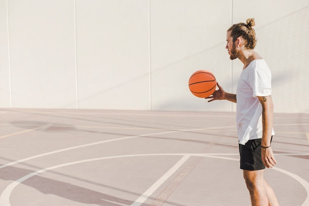 Side view of a man playing basketball in outdoor court