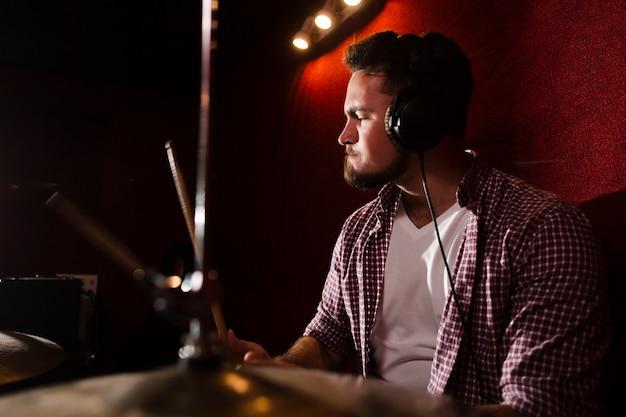Боковой вид человек играет на барабанах и носить наушники