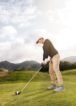 Side view of man playing golf on the field with club and copy space