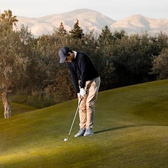 Vista laterale dell'uomo che gioca sul campo da golf erboso