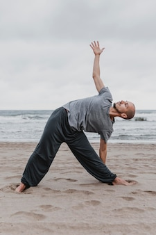 Side view of man practicing yoga positions outside