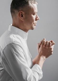 Uomo di vista laterale che prega alla divinità a casa