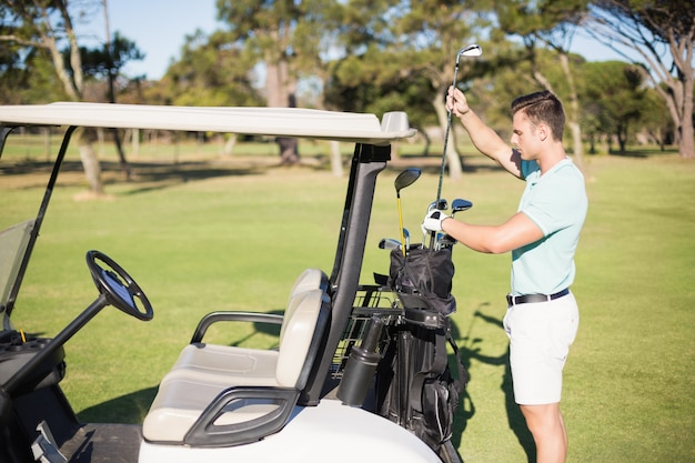 Side view of man putting golf club in bag