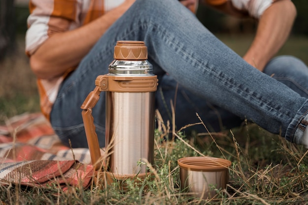 Vista laterale dell'uomo che si distende all'aperto con il thermos