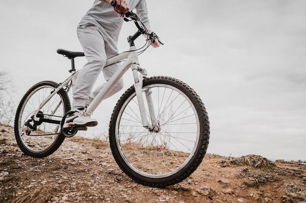 Вид сбоку человек, едущий на горном велосипеде