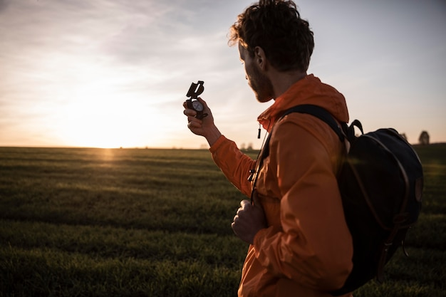 Side view of man on a road trip admiring the view while holding compass