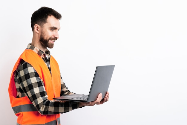 Side view of man in safety vest holding laptop