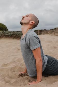 Vista laterale dell'uomo sulla sabbia che fa yoga