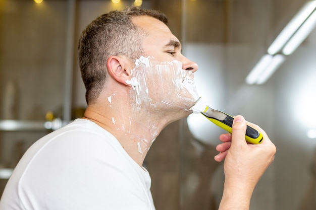 Side view man shaving in the bathroom