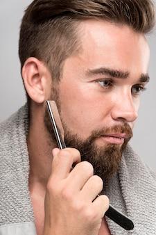 Side view man shaving his beard
