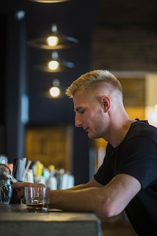 Side view of a man sitting at bar counter using cellphone