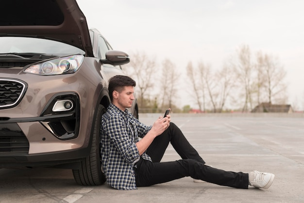 Side view man sitting next to broken car