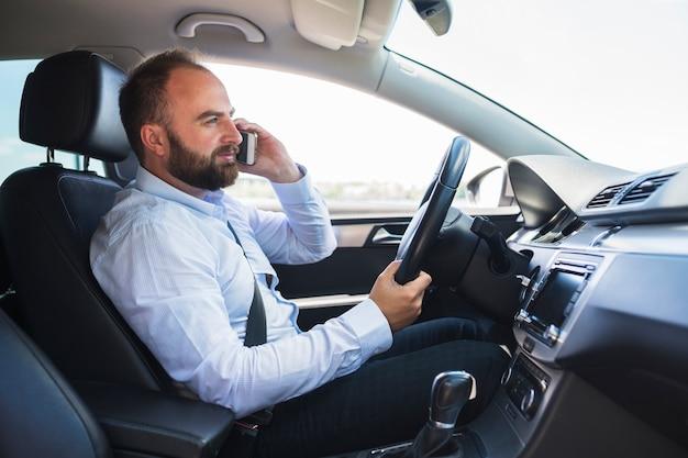 Vista laterale di un uomo seduto in macchina parlando sul cellulare