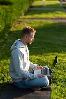 Uomo di vista laterale che si siede nella posizione del loto mentre lavora al computer portatile