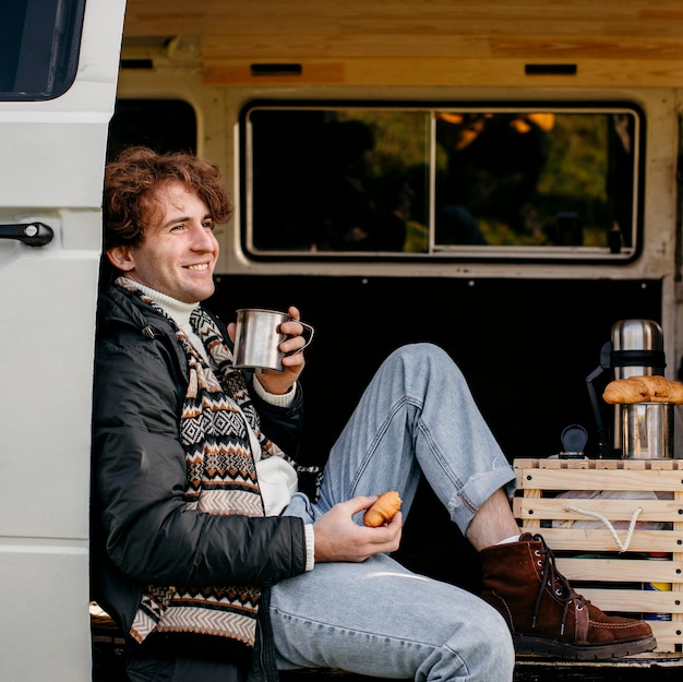 Side view man sitting in a van drinking his coffee
