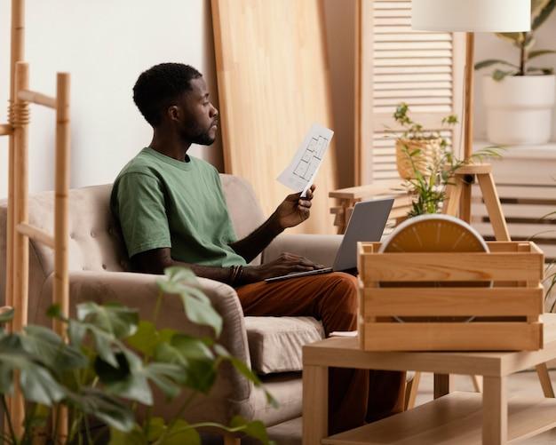 Vista laterale dell'uomo sul divano che fa un piano per ridipingere la casa
