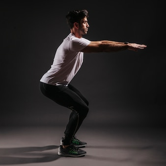 Side view man squatting on dark background