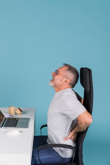 Side view of a man suffering from backpain while working on laptop