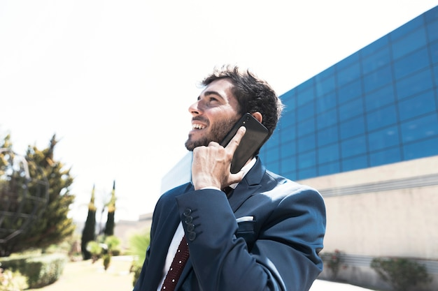 Side view man in suit talking on the phone