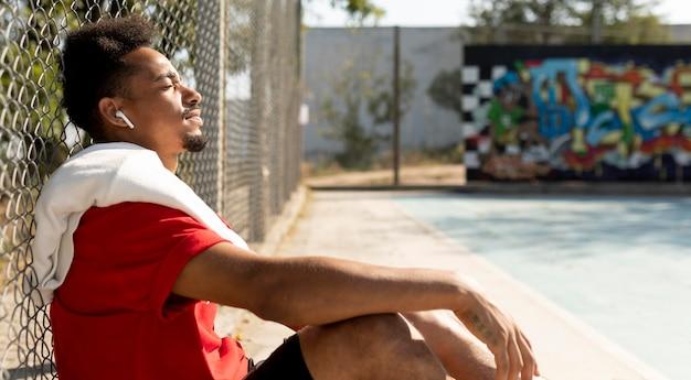 バスケットボールの試合後に休憩を取っている側面図の男