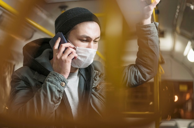 Side view of man talking on the phone in the bus while wearing medical mask