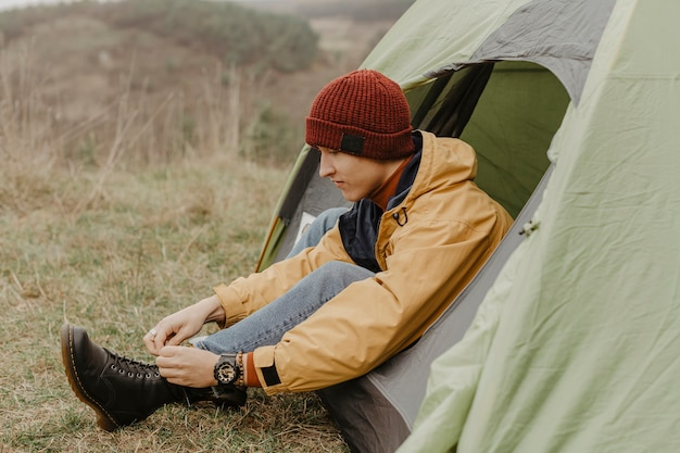 Side view man in tent binds laces