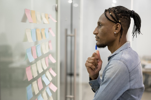 Side view of man thinking in office while looking at sticky notes