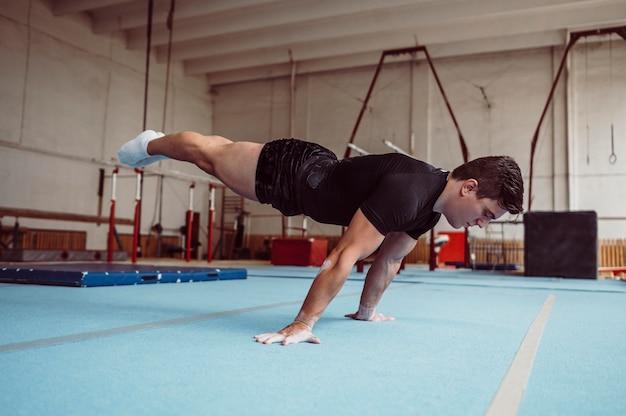 Тренировка человека с брусьями, вид сбоку