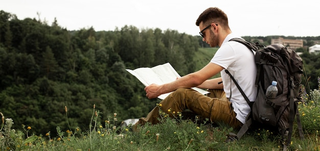 Side view man traveling alone reading map