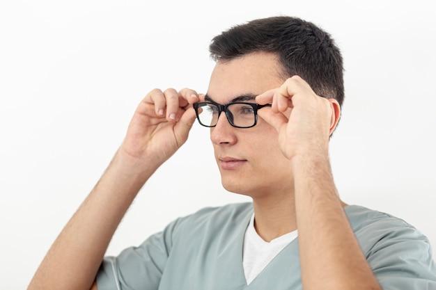 Vista laterale dell'uomo che prova sui suoi occhiali