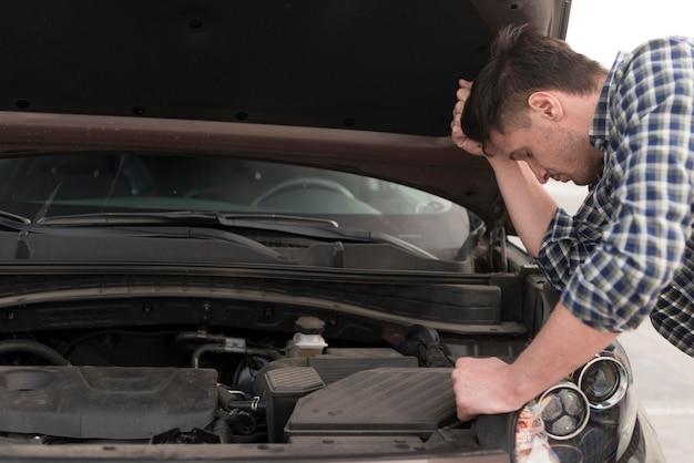 Боковой вид человек пытается отремонтировать автомобиль