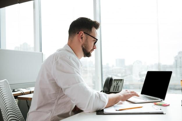 Side view of man using laptop
