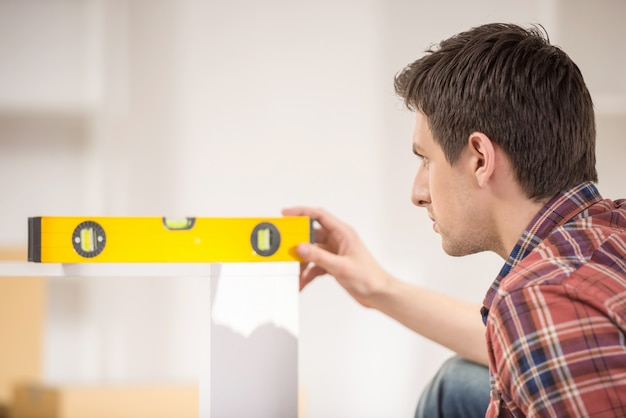 Side view of a man using spirit level at home.